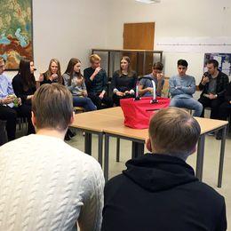 Ett 20-tal ungdomar sitter i en cirkel på stolar i ett klassrum