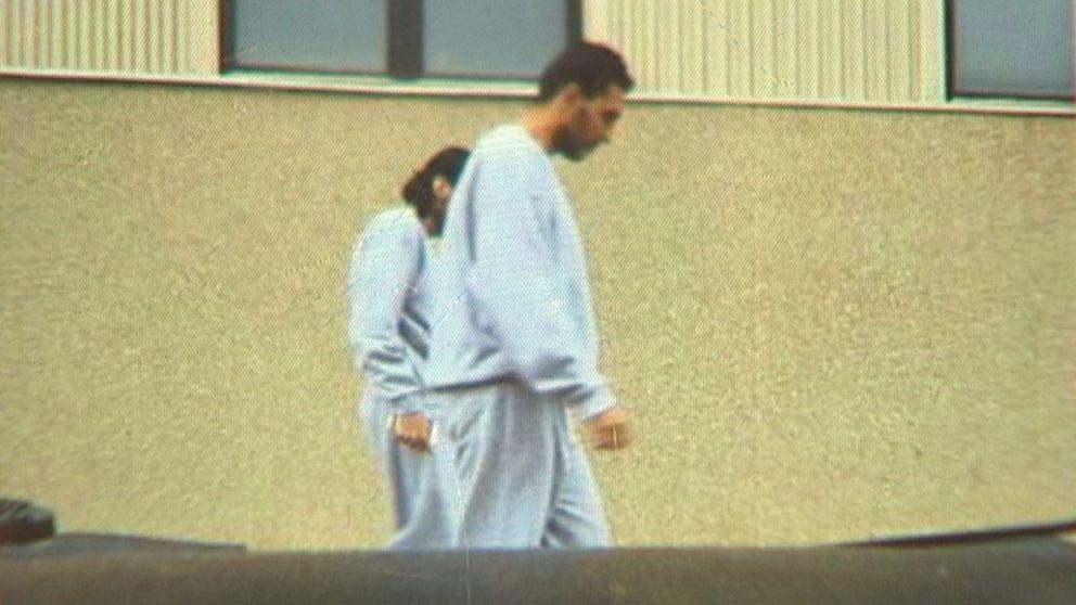 Tvä män i häkteskläder går utanför polishuset i Luleå