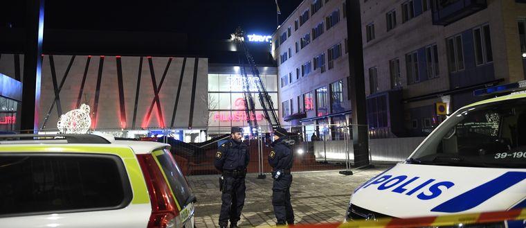Två poliser står bakom avspärrningsband bredvid polisbilar framför Täby centrum.