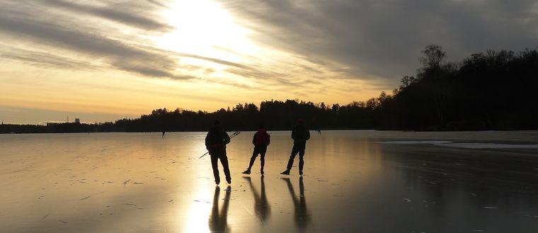 Personer som åker skridskor på isen
