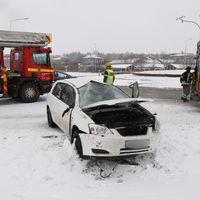 Räddningstjänsten är på plats vid en trafikolycka. En vit personbil i förgrunden med krossat framruta och öppen motorhuv.