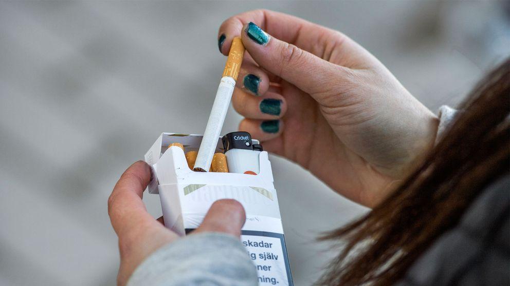 en tjej plockar upp en cigarett ur en förpackning