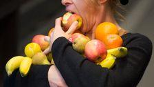 Kvinna med famnen full av frukt tar en tugga ur ett äpple