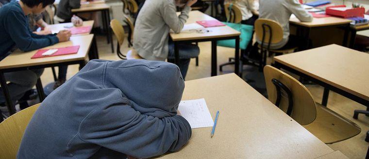 En pojke som ligger över en bänk med händerna över huvudet.
