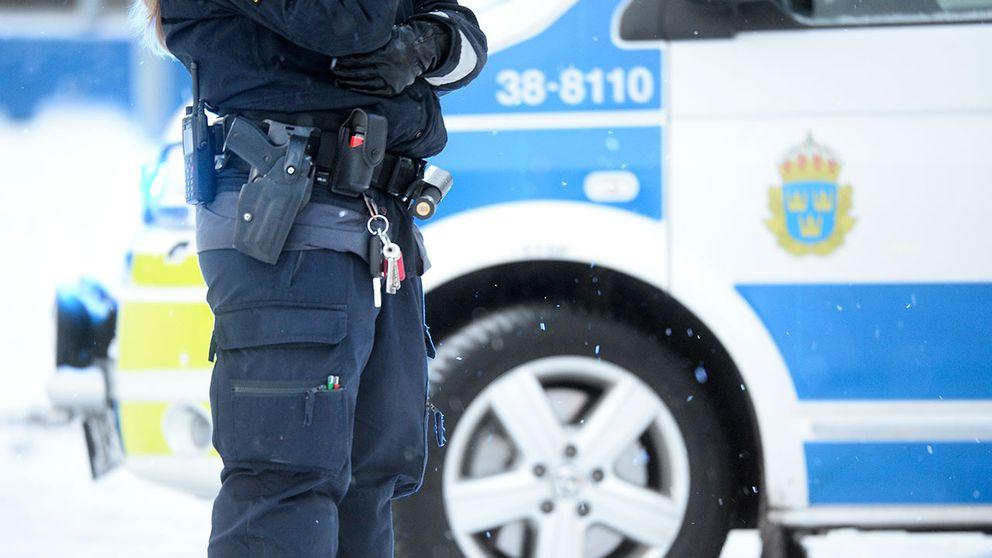 Polis vid en polisbil.