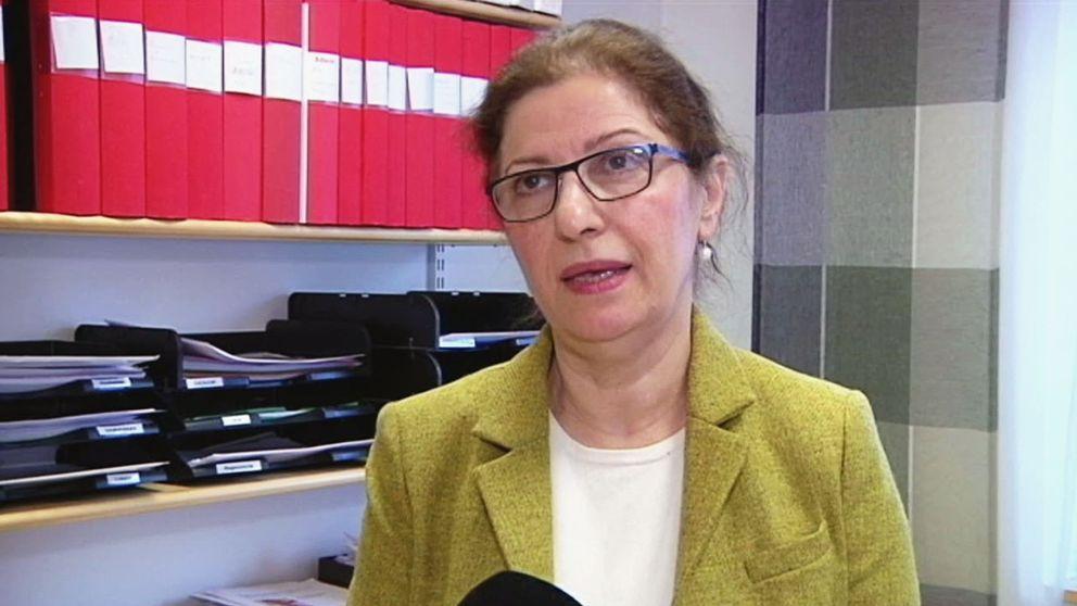 Kvinna med mörkt uppsatt hår och glasögon står i sitt kontor.