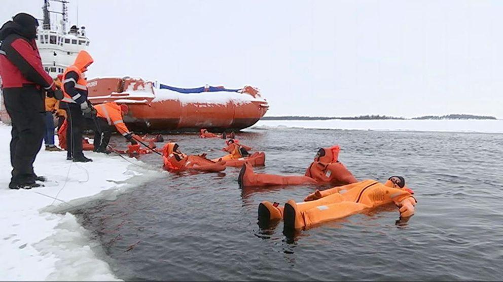 Personer flyter omkring i oreanga dräkter i isvak.