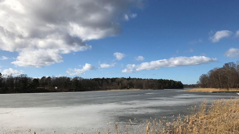 Moln över sjön Magelungen i Farsta. Isen spricker upp.