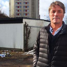 Thomas Bodström står framför en låg vit byggnad, resterna från en gammal minnesplats syns i bakgrunden.