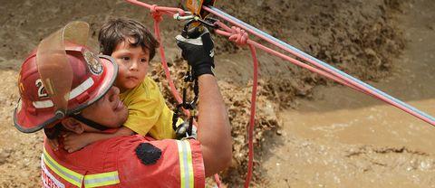 En liten pojke får hjälp av räddningstjänst att ta sig över en våldsamt forsande vattenmassa i Huachipa, öster om huvudstaden Lima.