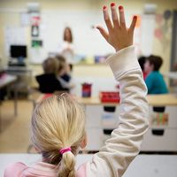Karta där Borås och Åbo är markerat. En flicka sitter i ett klassrum och räcker upp handen.