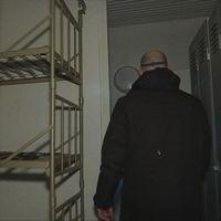 Man i svart jacka går förbi två våningssängar i smal korridor