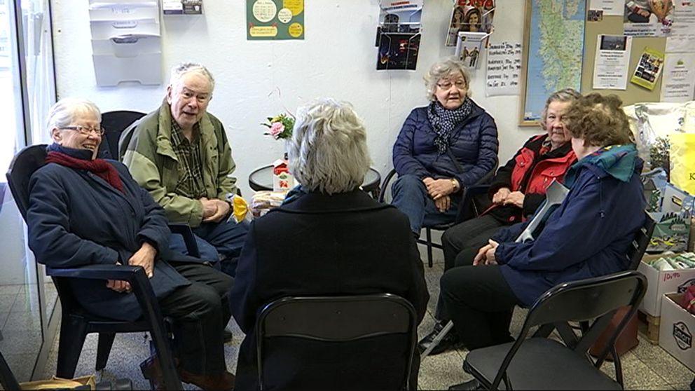 Sex pensionärer sitter samlade runt ett fikabord.