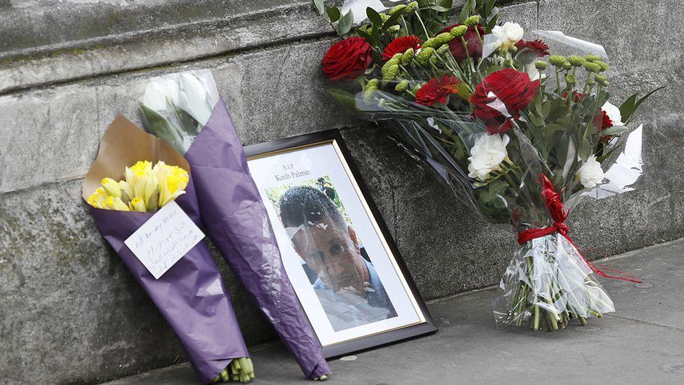 Blombuketter intill ett foto av den mördade polisen