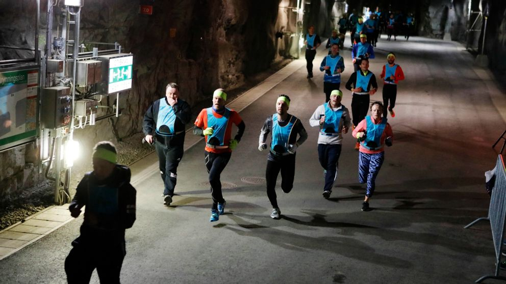 Joggare i färgglada kläder springer nere i den långa tunneln.