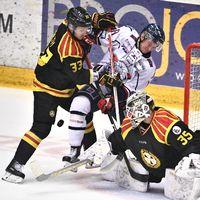 Tre män med hockeyutrustning som tacklas i jakten på en puck.