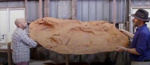 Två män bär en fossil av ett dinosauriefotspår
