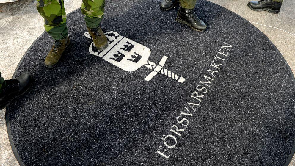 Militärer står på en matta där det står Försvarsmakten.