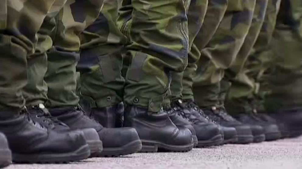 soldaters ben med kamouflagebyxor och kängor