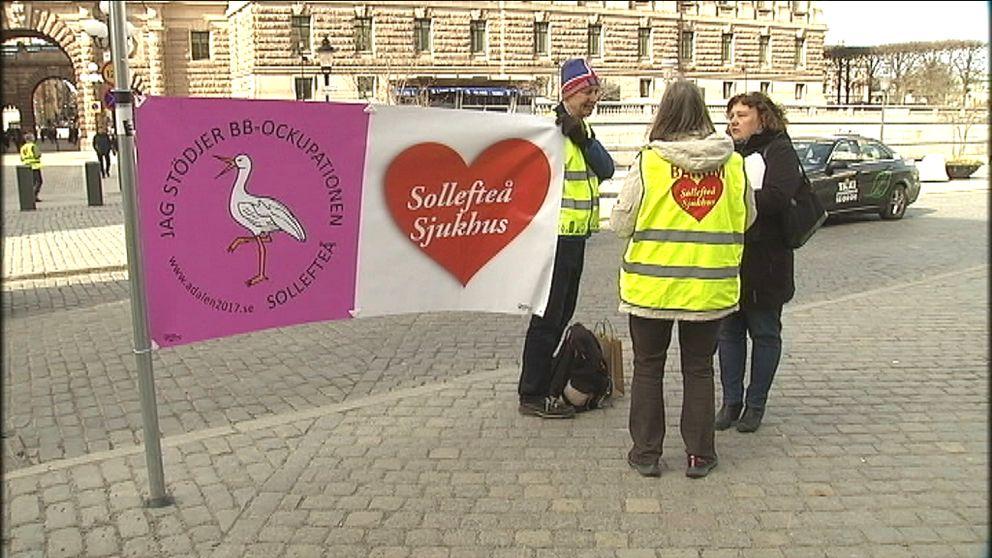 Tre aktivister från Sollefteå med banderoller med texten Jag stödjer BB-ockupationen Sollefteå, framför riksdagshuset.