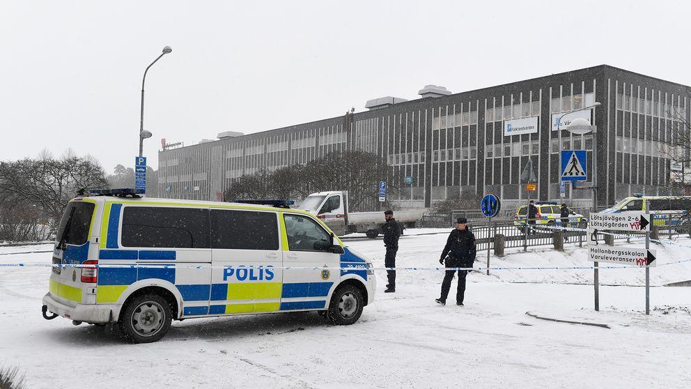 Bild från brottsplatsen i Hallonbergen. Polisbil och två poliser syns på bilden.