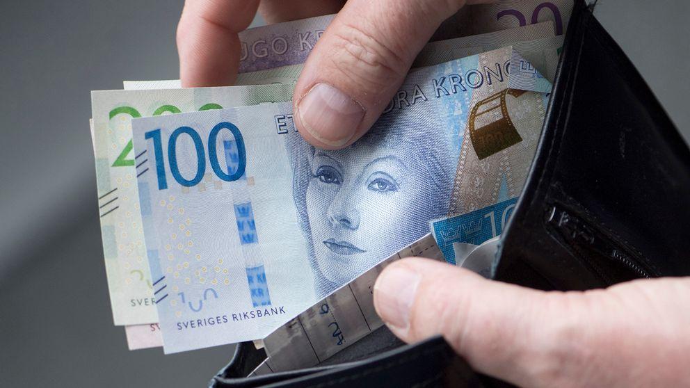 hand tar fram sedlar ur plånbok