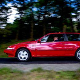 En röd bil kör på en väg