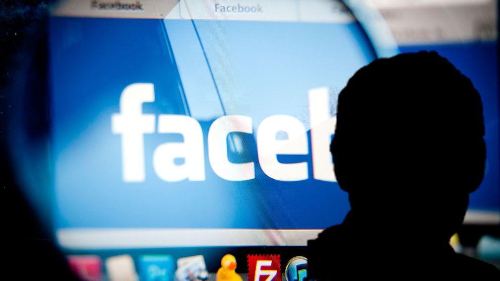En silhouette framför Facebooks logotyp på en datorskärm.