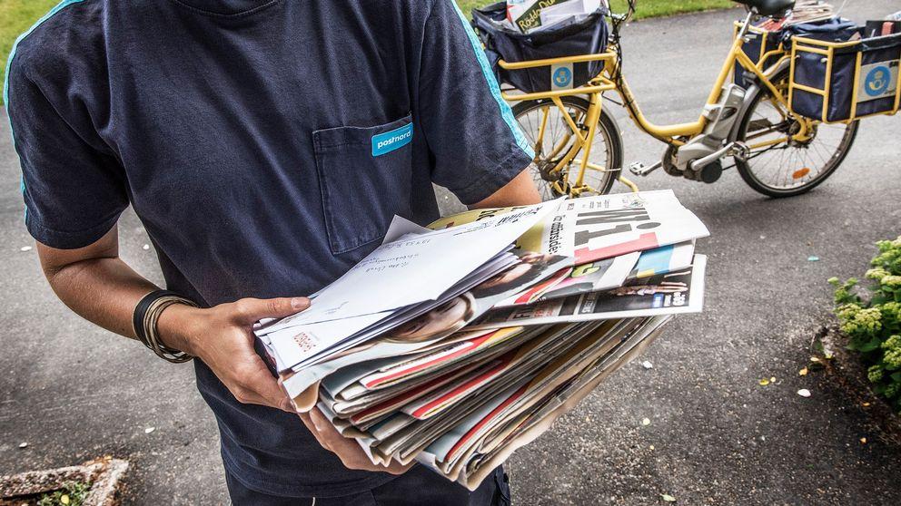 Brevbärare håller post i famnen, i bakgrunden en postcykel.