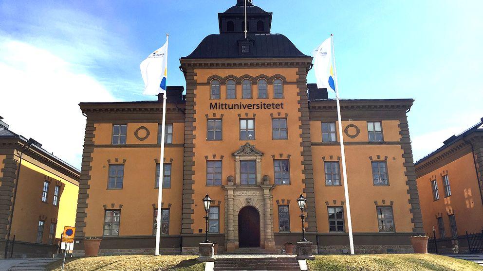 vy över universitetet – pampig äldre byggnad, flaggor framför