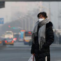 En kvinna i andningsmask står på en gata i Peking, Kina.