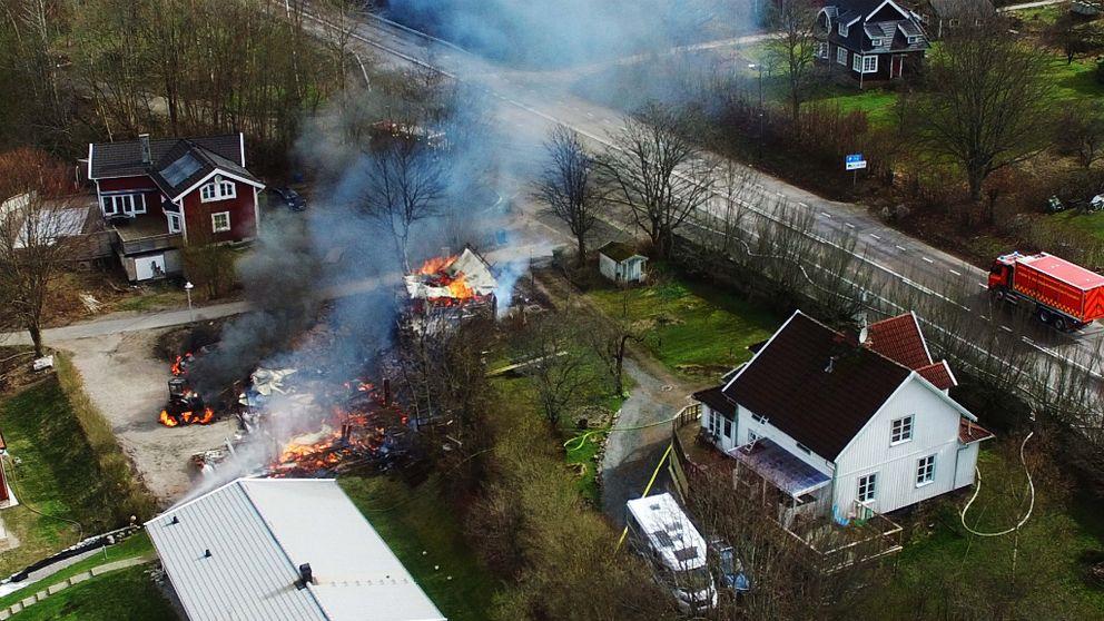 En fullt utvecklad brand rasar i en bilverkstad i Frufällan. Polisen har spärrat av ett stort område på grund explosionsrisk.