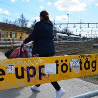 """Familj passerar över spåret vid Södra station i Örebro. I förgrunden en skylt med texten """"se upp för tåg""""."""