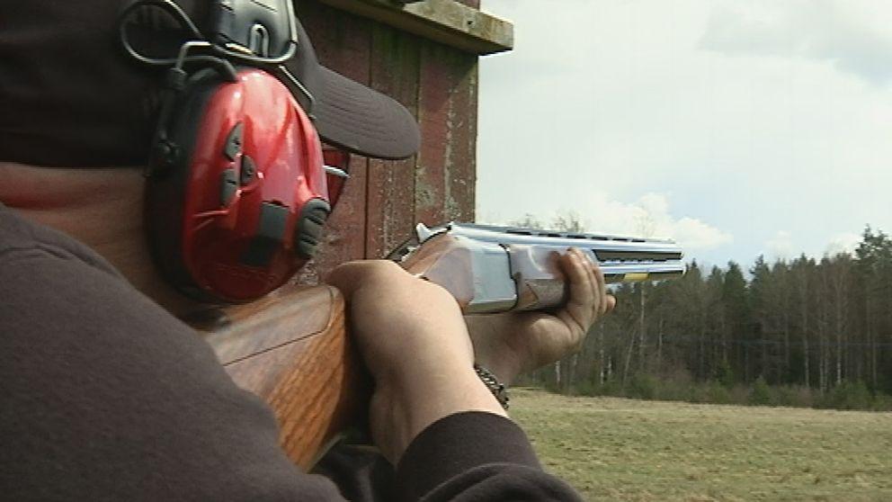 En man siktar med ett hagelgevär.
