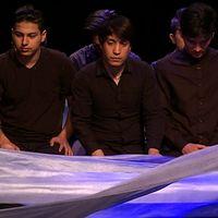 Fem unga killar sitter bredvid varandra på golvet med ett blått tygstycke som fladdrar i förgrunden. Scenen föreställer båtresan till Sverige över Medelhavet.