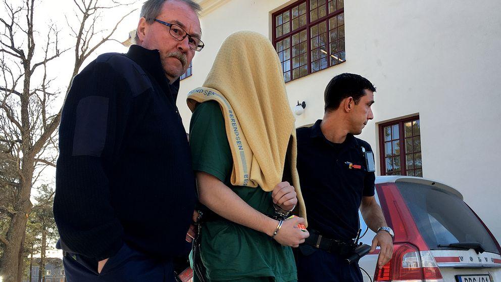 Den misstänkte mannen har en gul filt över huvudet när han förs in till rättegången av två väktare.