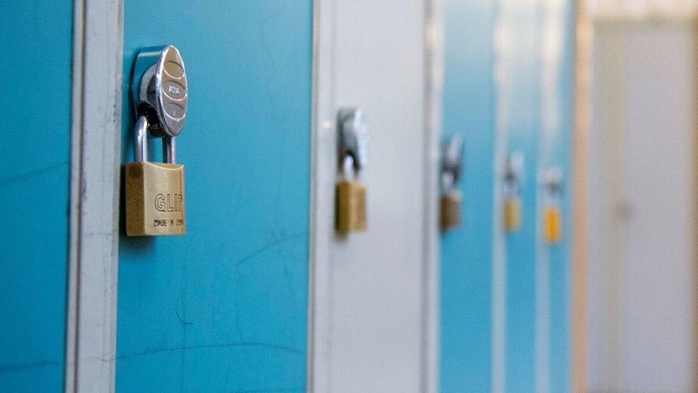 En elev går i en skolkorridor med blåa skåp