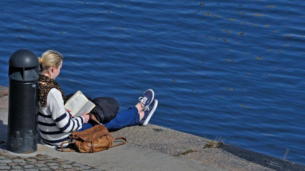 En kvinna sitter vid vattnet i solen och läser