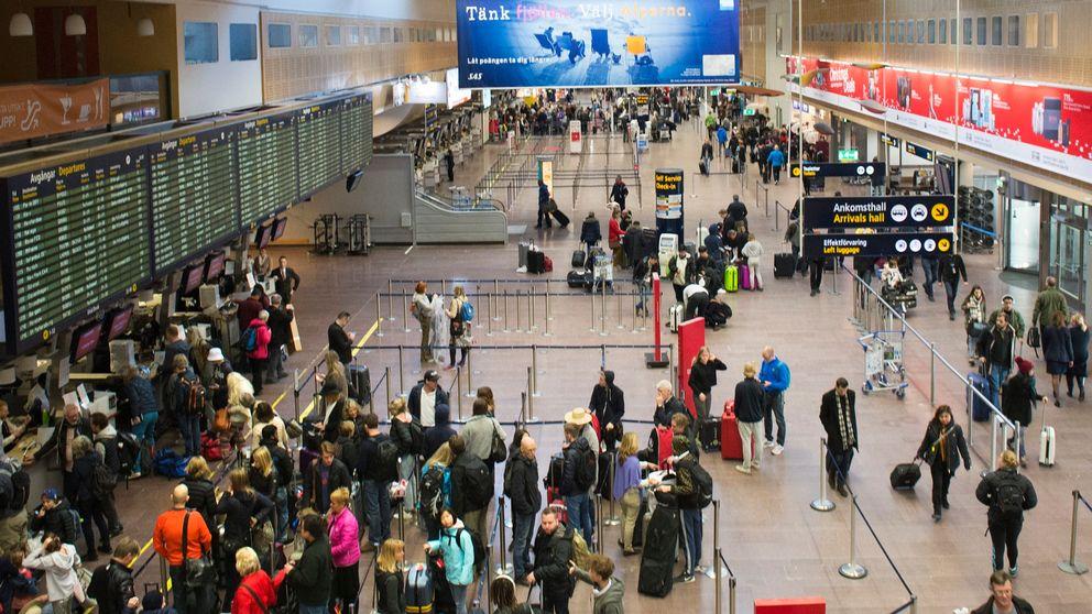 Avgångshallen på Arlanda sedd uppfrån. Folk rör sig i hallen, andra checkar in. Till vänster tavlor med avgångstiderna