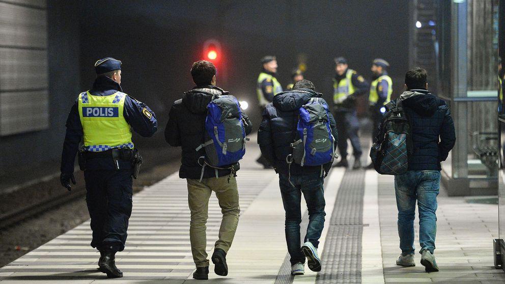 Polis eskorterar asylsökande efter genomförd gränskontroll.