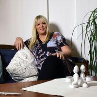 en leende kvinna sitter i soffa i hemmiljö