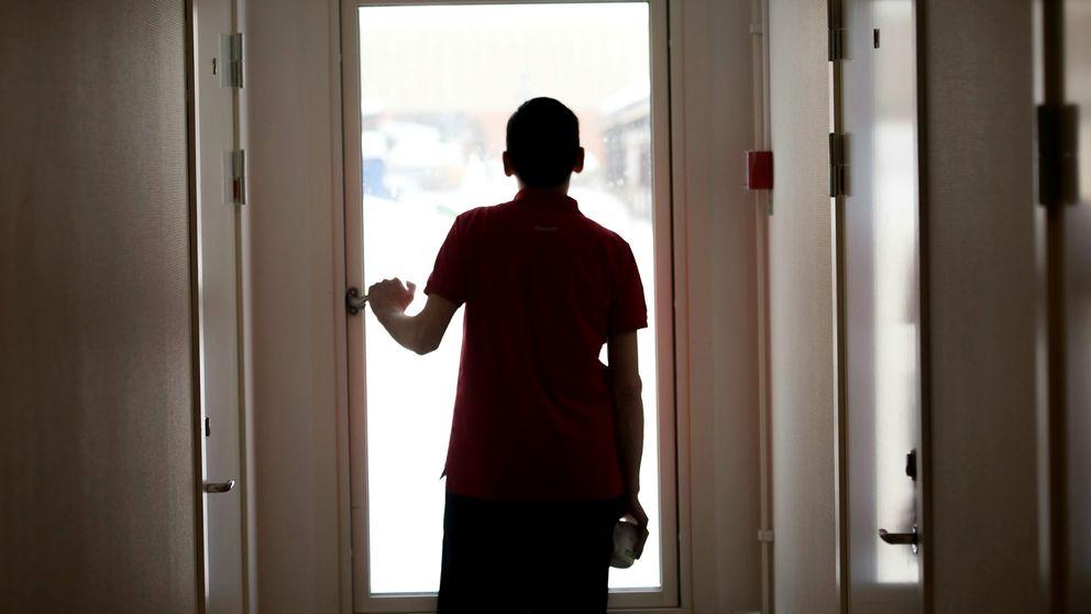 Pojke som står ensam framför en stor glasdörr