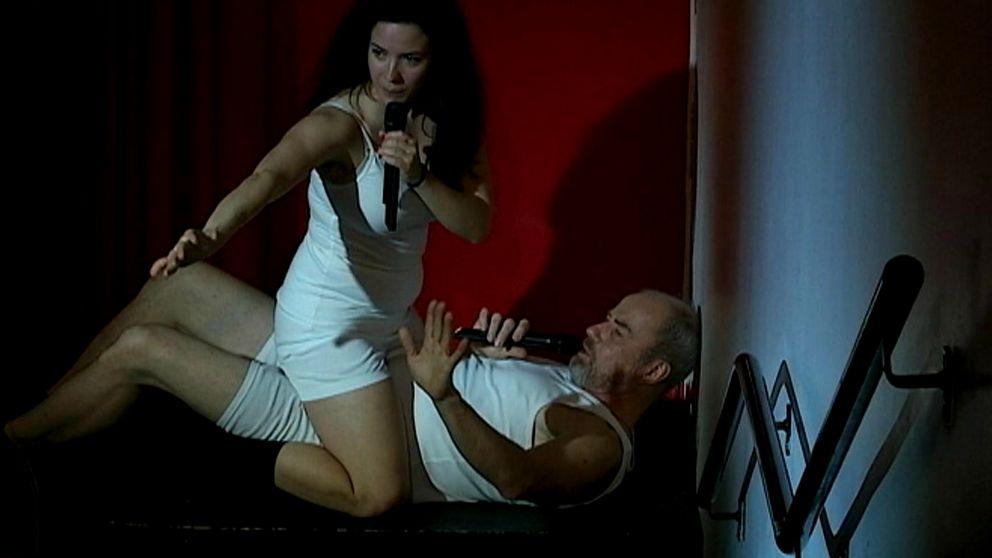 Skådespelaren Lennart Jähkel ligger på rygg och linne och kalsonger med en kvinna som sitter gränsle över honom.