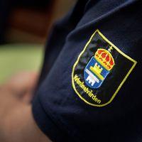 kriminalvården, logga, arbetskläder, blå skjorta, närbild, skjortärm