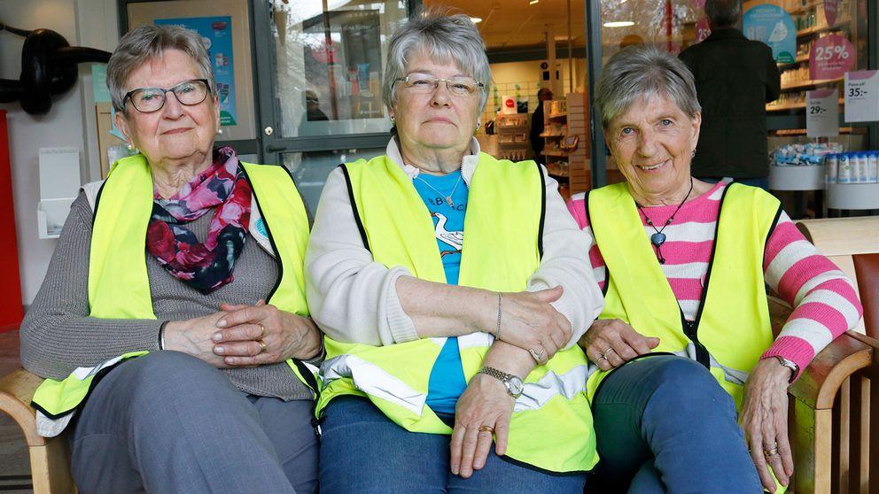 tre äldre kvinnor med varselvästar sitter på bänk