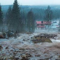 vatten forsar över mark ner mot hus