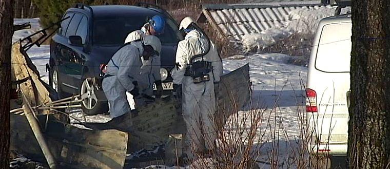 personer i skyddskläder, två bilar, vid brunnet hus