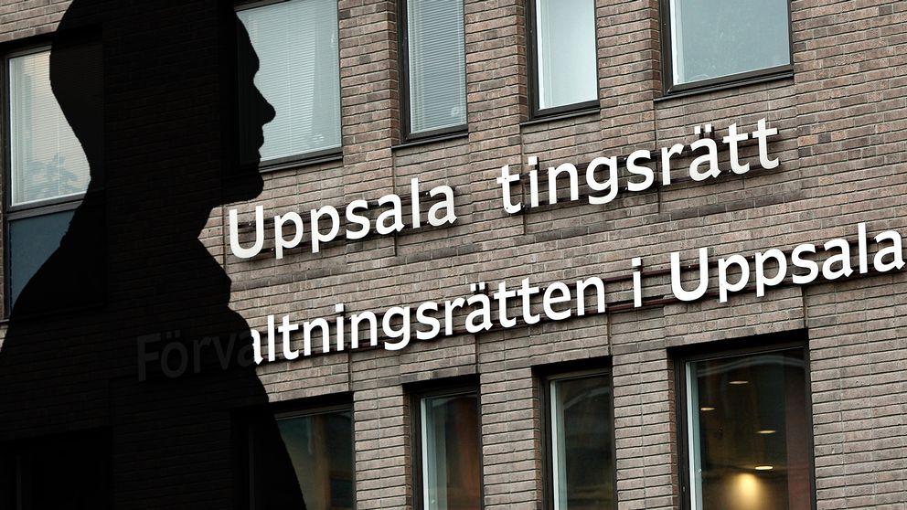 Fotomontage, en svart silhuett av en man över en bild på Uppsala tingsrätt.
