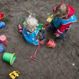 Två barn leker på i en sandlåda