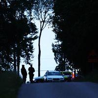 Poilser och polisbilar på en väg sen kväll.